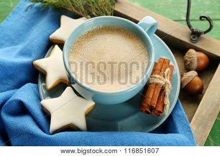 Cup of coffee with star shaped biscuits on napkin on wooden tray