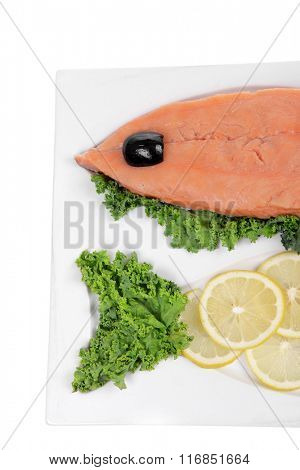 healthy food - fresh raw red fish with kale lemon and black olives on plate isolated on white background space for text