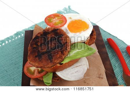 junk food big beef hamburger on dark wood plate with modern cutlery on blue mat isolated over white background