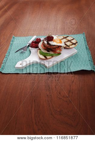 junk food meat big beef hamburger fried eggs on white  wood plate with cutlery ketchup sauce and pickles on blue mat over wooden table