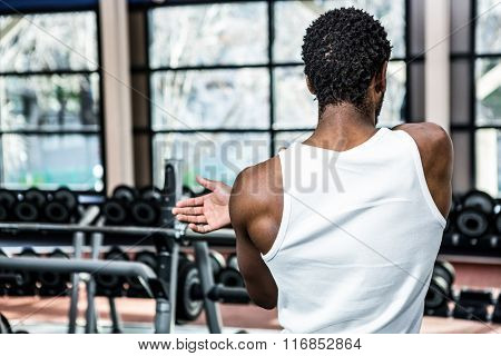 Rear view of man stretching arms at gym