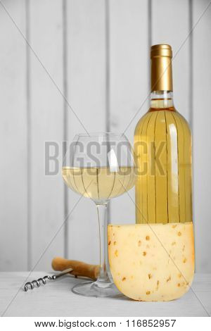 Wine and cheese on wooden wall background