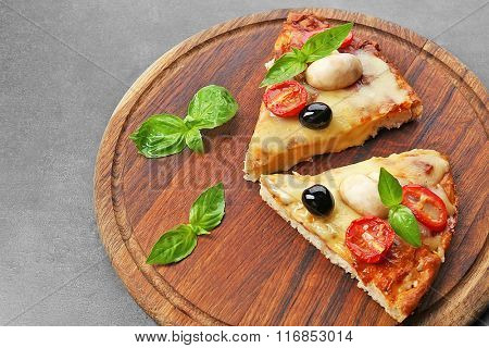 Slices of tasty pizza on round wooden board, close up