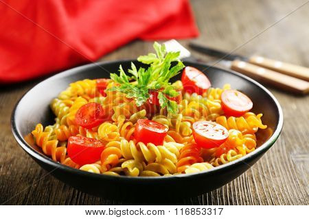 Delicious macaroni dish in black bowl on served wooden table