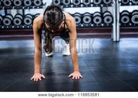 Fit woman doing push ups exercises at gym