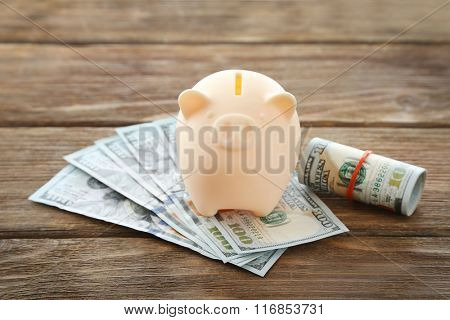 Piggy bank with rolled dollars on wooden background