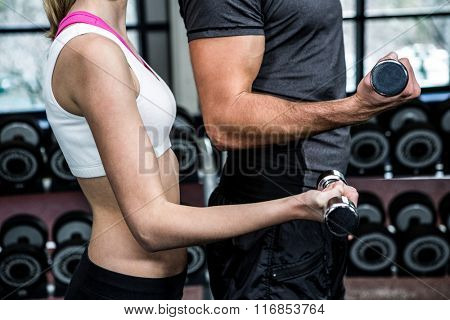 Cropped image of fit couple lifting dumbbells at gym