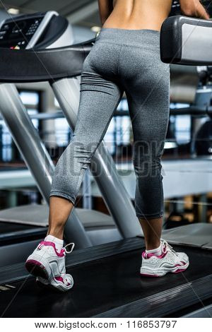 Mid section of woman using treadmill at gym