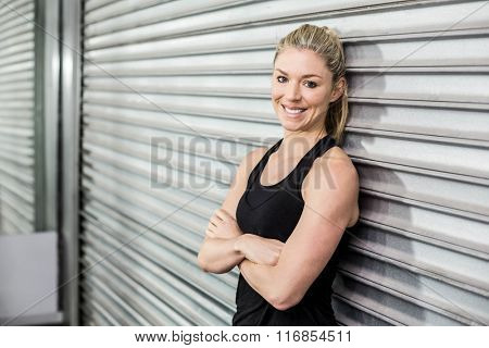 Fit woman with arm crossed at crossfit gym