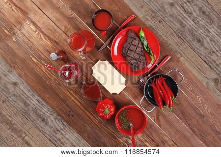 red theme lunch : fresh grilled bbq roast beef steak red plate green chili tomato soup ketchup sauce paprika small glass pepper american peppercorn modern cutlery served wooden table empty nameplate