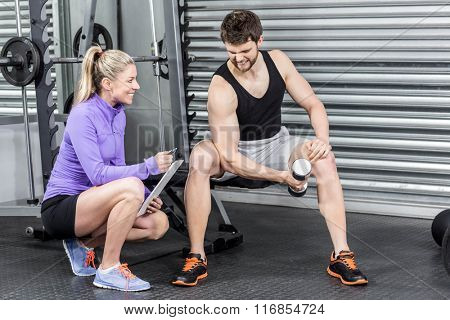 Female trainer assisting man with dumbbells at crossfit gym