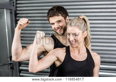 Fit couple showing muscular arms at crossfit gym