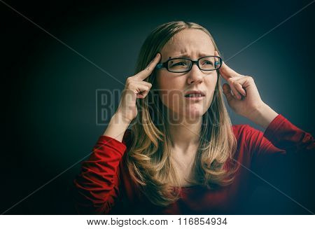 Portrait of a young girl in a red dress on a gray background. Portrait stressed sad young woman eyes closed hands touching head. LOMO effect