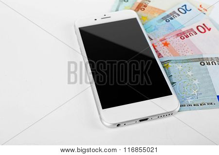 Smart phone with euro banknotes, isolated on white Internet earning concept