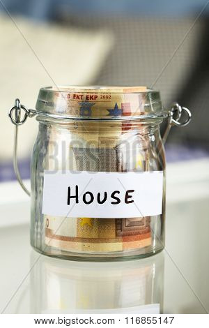 Glass jar with euro banknotes for house on a table