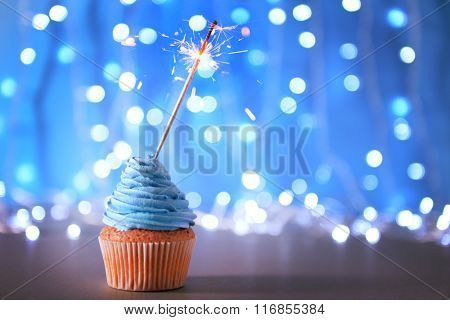 Cupcake with blue cream icing and sparkler on a glitter background