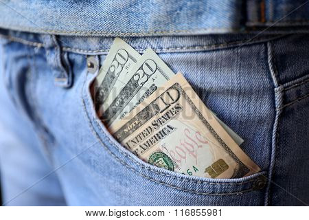 Dollar banknotes in jeans pocket closeup