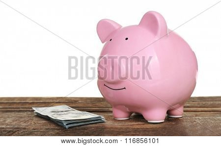 Piggy bank with banknotes on wooden table, isolated on white