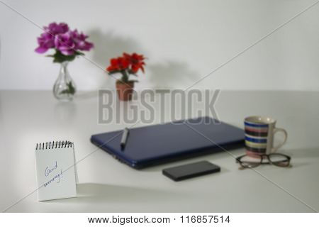 Good Morning Written On Notebook Over Blurry Business Still Life Background
