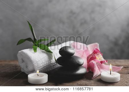 Spa stones with pink orchid, candles, bamboo and towel on wooden table against grey background