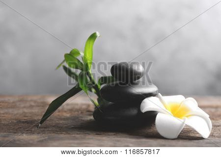 Spa stones with bamboo and tropical flower on wooden table against grey background