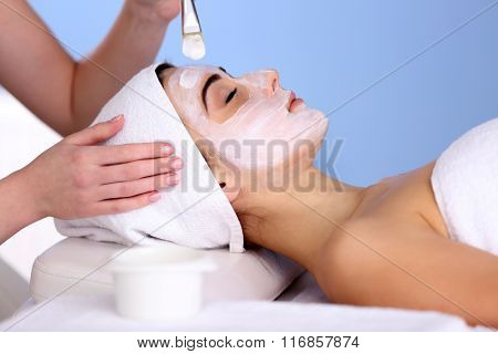 Spa concept. Young woman with facial mask in beauty salon, close up