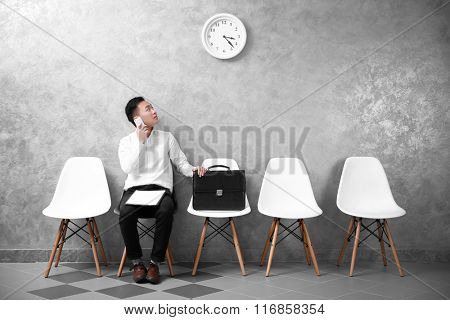 Young Asian businessman sitting on a chair and looking at the clock in grey hall