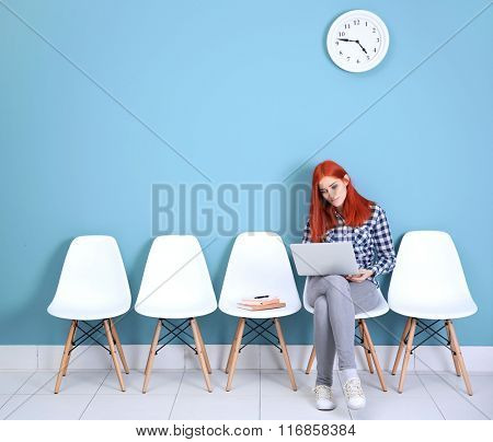 Young redhead girl sitting on a chair and using laptop in blue hall
