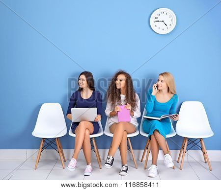 Young girls sitting on a chairs and looking right in blue hall