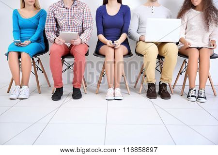 Young people with devices sitting  on a chairs in white hall, close up