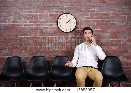 Young businessman sitting on a chair and talking on smart phone in brick wall hall