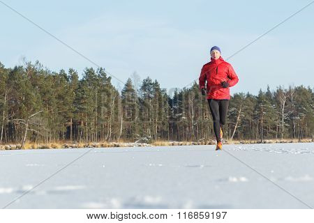 Young man running outdoors in winter snowy sunny forest