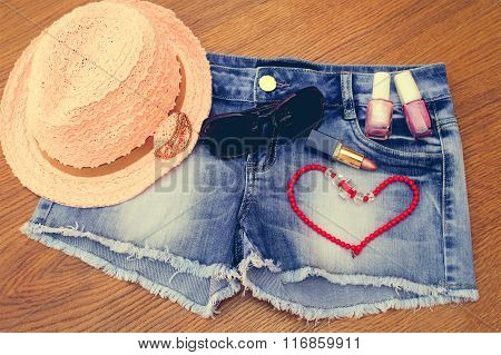 Summer women's accessories: red sunglasses , beads, denim shorts, sun hat, nail polish, lipstick ope