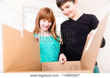 Children unpacking boxes in new home