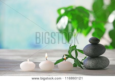 Spa stones with candles and bamboo on blurred background