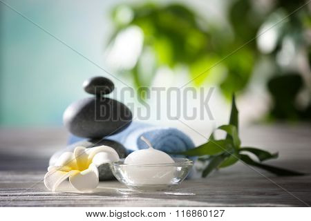 Spa stones with towel, tropical flower, bamboo and candle on blurred background
