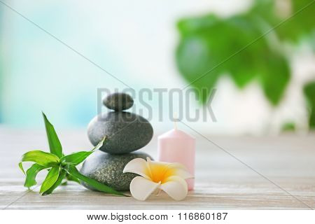 Spa stones with candle, bamboo and tropical flower on blurred background