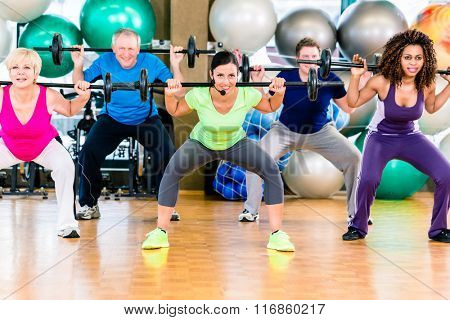 Men and women lifting barbell in gym, diversity group of old, young, black and white people