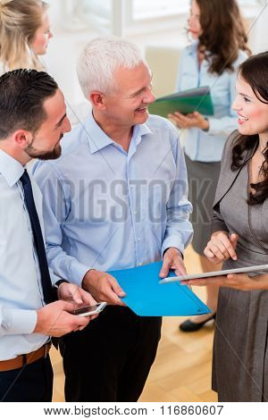 Business woman in office showing boss presentation, more business people standing in the background