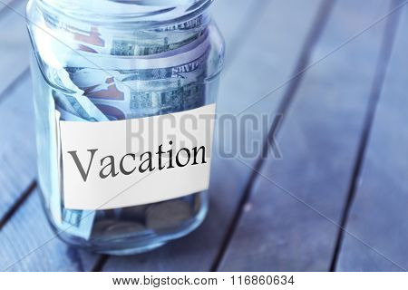 Savings in glass bank on wooden background