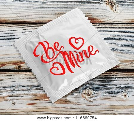 Condom with text Be mine on wooden table