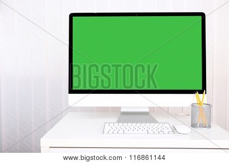 Modern computer with green screen, on table