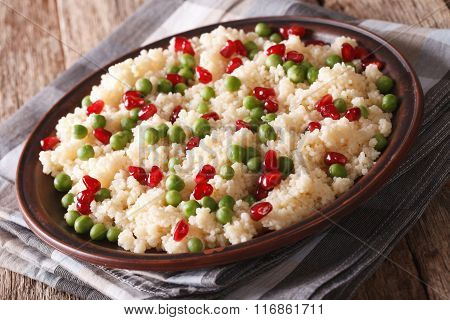 Couscous Salad With Green Peas And Pomegranate Close-up. Horizontal