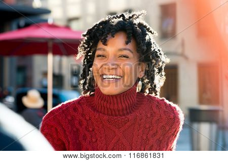Closeup of an african young woman laughing outdoor. Happy young smiling african woman in cafe. Potrait of a young joyful african woman smiling outdoor in a sunny day.