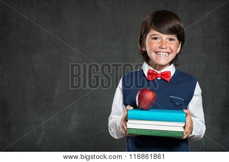 Closeup of little boy holding stack of books and apple. Happy schoolboy smiling and looking at camera. Cheerful child holding books with red apple standing isolated on blackboard with copy space.