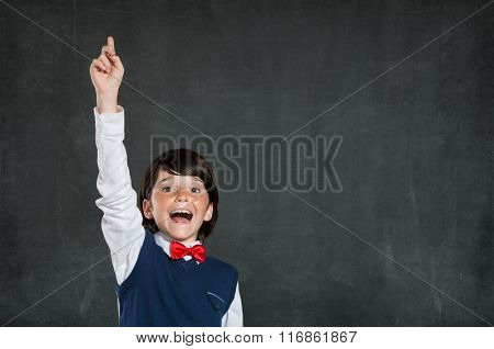 Closeup of little boy with raised hand isolated on blackboard. Schoolboy pointing high his index finger. Cheerful cute boy with raised hand standing against black background.
