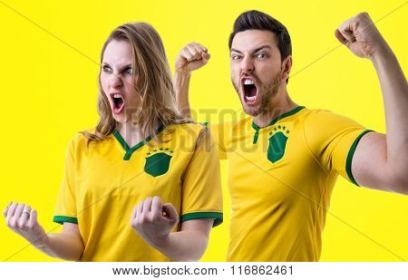 Brazilian couple fan celebrating on yellow background