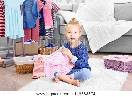 Little girl in the room with a lot of new clothes