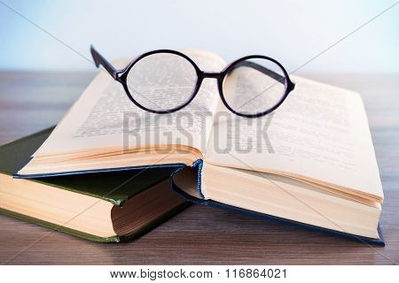 Books and eyeglasses on wooden table, close up