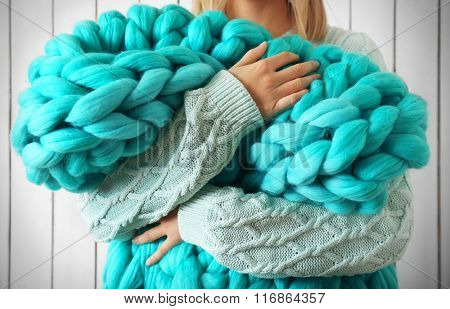 Woman wrapped in large knitted blanket